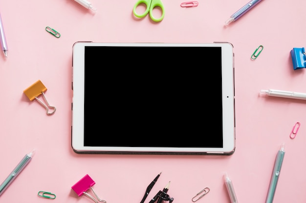 Tablette numérique entourée de divers articles sur fond rose