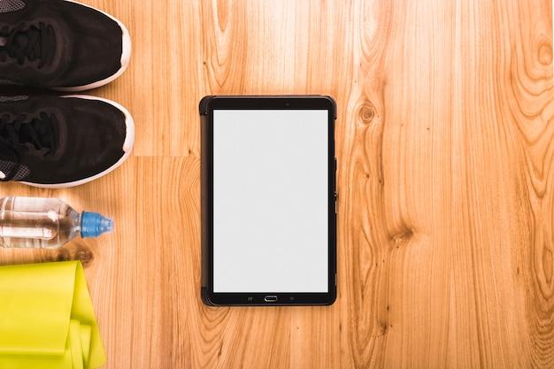 Tablette numérique et équipements de fitness sur plancher en bois