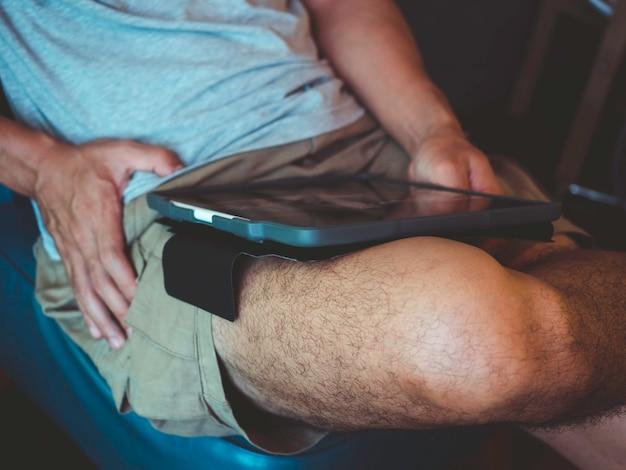 Tablette numérique sur les genoux de l'homme en chemise grise décontractée et short assis et interagissant avec la technologie à la maison. homme d'affaires décontracté de détente travaillant en ligne à n'importe quel concept.