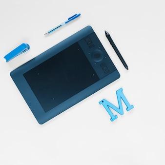 Tablette numérique graphique; stylo; agrafeuse et m alphabet sur la surface blanche