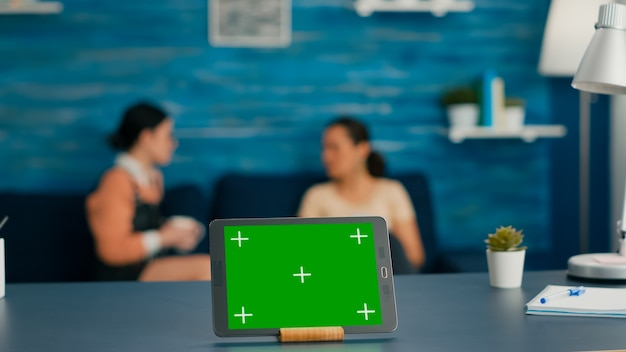 Tablette numérique isolée avec affichage de la clé chroma à écran vert simulé debout sur le bureau dans le salon. en arrière-plan, des collègues parlent de communication en ligne