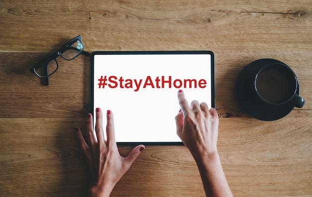 Une tablette numérique avec la main, avec le texte restez à la maison sur l'écran
