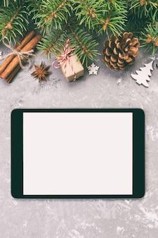 Tablette numérique maquette avec des décorations de ciment de noël gris rustique pour présentation de l'application, vue de dessus,