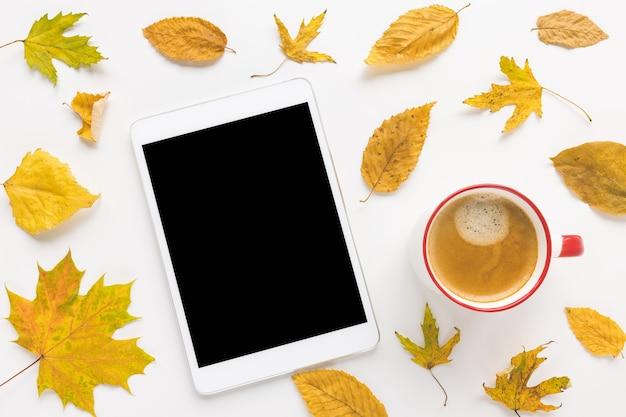 Tablette numérique maquette tasse d'espresso avec crème et feuilles d'automne jaune sur fond blanc automne