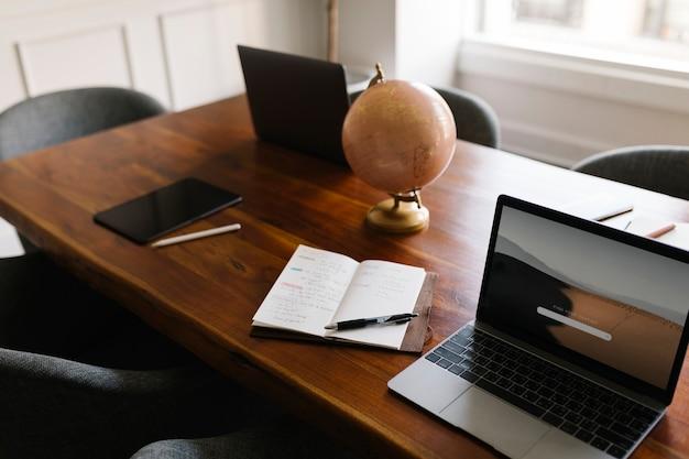 Tablette numérique et ordinateurs portables sur une table en bois dans une salle de réunion