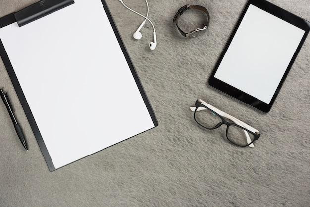 Tablette numérique; presse-papiers; écouteur; montre-bracelet; lunettes et stylo sur fond gris