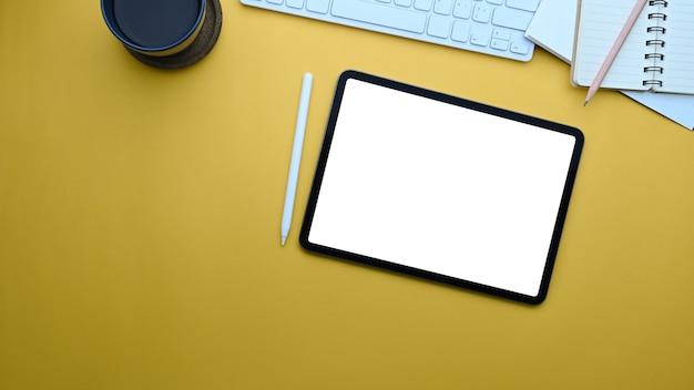 Tablette numérique, stylet, bloc-notes et tasse à café sur fond jaune.