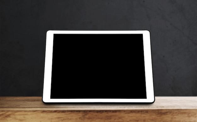 Tablette numérique sur une table en bois avec mur noir