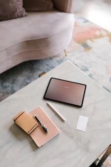 Tablette numérique sur une table en marbre blanc dans un salon