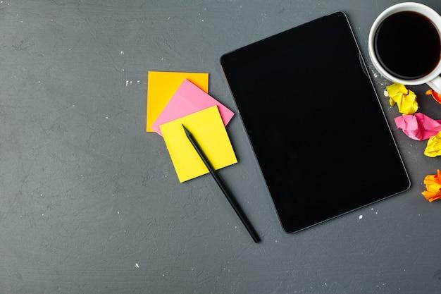 Tablette numérique et tasse de café sur un bureau en bois.