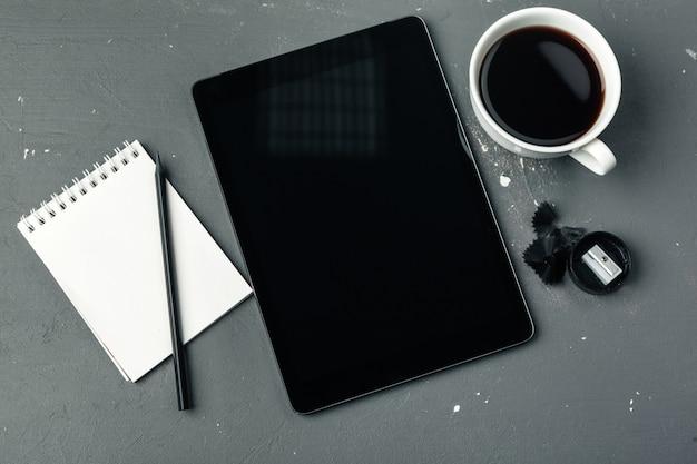 Tablette numérique et tasse de café sur le bureau en bois.