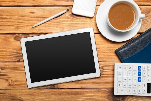 Tablette numérique et tasse à café sur table en bois