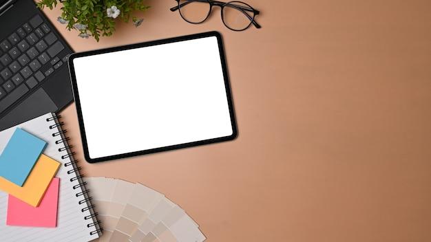 Tablette numérique vue de dessus, notes de bâton et lunettes sur l'espace de travail du concepteur.