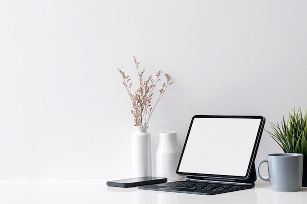 Tablette d'ordinateur à écran blanc et clavier avec plantes et tasse sur table de travail.