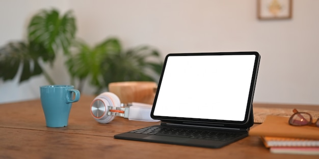 Tablette d'ordinateur à écran blanc avec un étui à clavier est mise sur un bureau en bois.