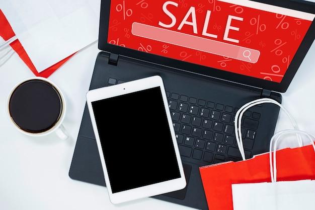 Tablette, ordinateur portable, café et sacs à provisions sur fond clair. concept d'achat en ligne