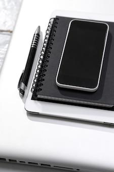 Tablette, ordinateur, smartphone, bloc-notes et stylo sur la table