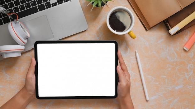 Tablette d'ordinateur vue de dessus à portée de main avec une offre créative sur une table en marbre jaune.