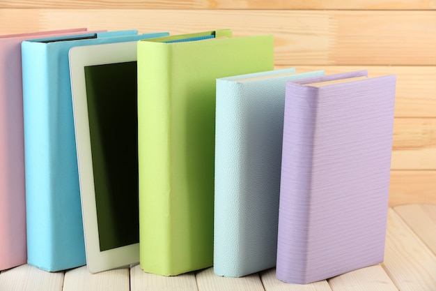 Tablette pc et livres sur table en bois, sur fond de bois