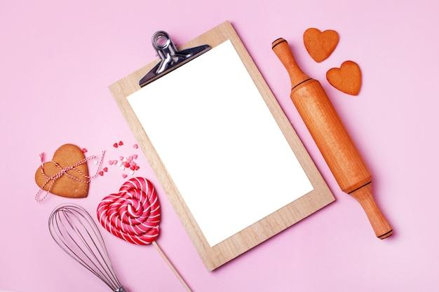 Tablette pour écrire des recettes de pâtisserie, rouleau à pâtisserie et biscuits en forme de cœur sur fond rose. concept pour la saint-valentin. style plat