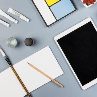 Tablette près de papier, crayon et tubes