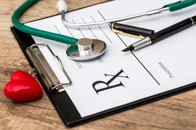 Tablette avec une recette de pharmacie avec un stéthoscope, un stylo et un coeur de jouet