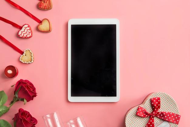 Tablette et roses, sur fond rose. vue de dessus.
