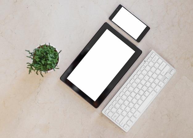 Tablette et smartphone avec écrans vierges sur table lumineuse