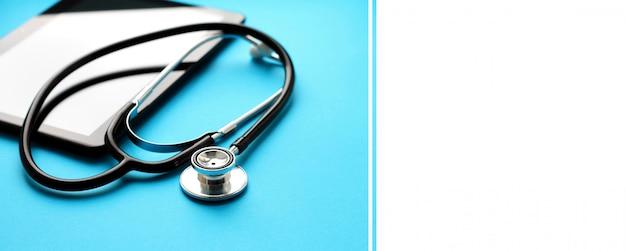 Tablette et stéthoscope sur blanc bleu. bannière.