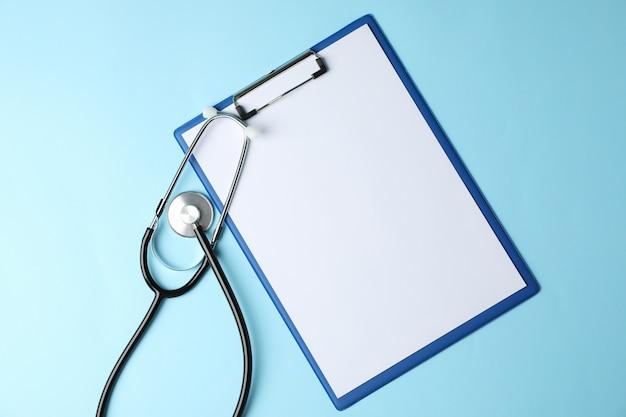 Tablette et stéthoscope sur bleu, vue de dessus et espace pour le texte