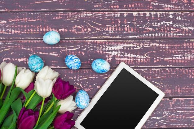Tablette, tulipes colorées et oeufs de pâques sur une surface en bois