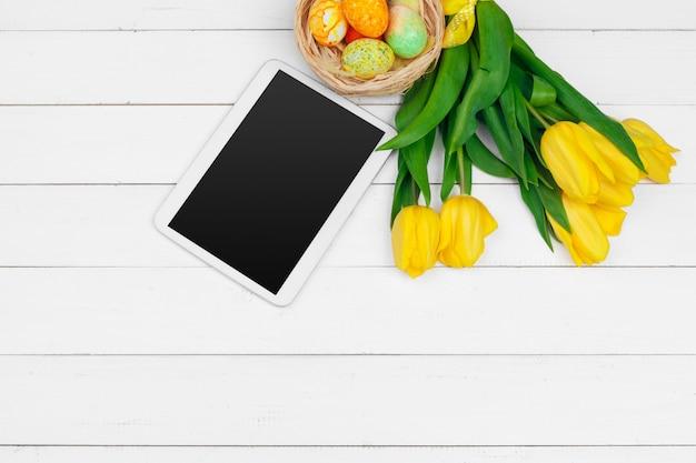 Tablette, tulipes jaunes et oeufs de pâques sur une surface en bois