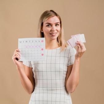 Tablettes et calendrier de période tenus par une femme