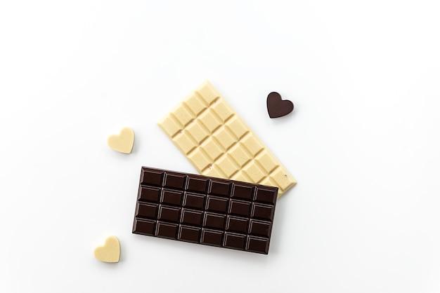 Tablettes de chocolat blanc et noir avec des coeurs sur fond clair.