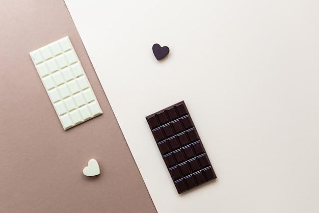Tablettes de chocolat blanc et noir avec des coeurs sur fond marron.
