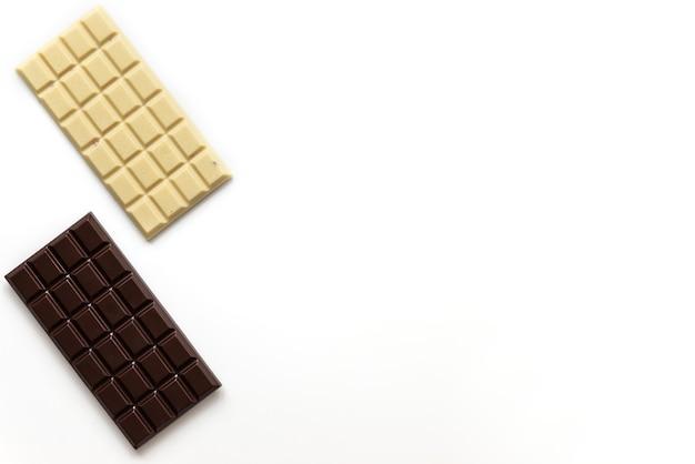Tablettes de chocolat blanc et noir sur fond blanc. orientation horizontale, espace copie, vue de dessus.