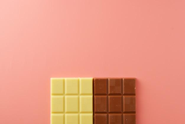 Tablettes de chocolat blanc et noir sur rose