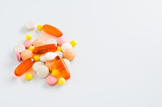 Tablettes colorées assorties, pilules, médicaments sur fond blanc