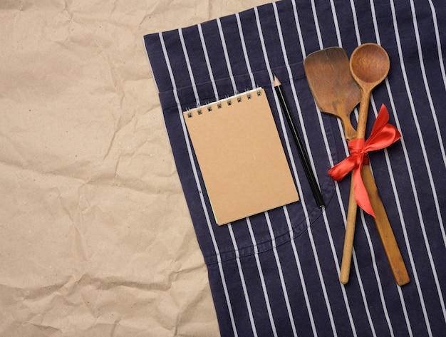 Tablier de chef bleu, cuillères en bois et cahier avec des feuilles brunes vierges, vue du dessus
