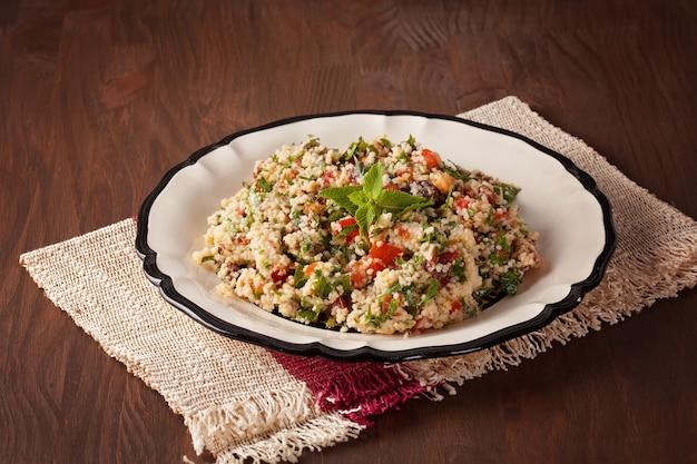 Taboulé - plat végétarien du moyen-orient avec couscous, tomates, persil, raisins secs et menthe assaisonnés d'huile d'olive et de jus de citron. recette authentique facile