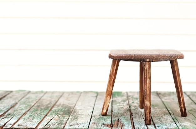 Tabouret en bois sur une vieille table en bois vintage sur un arrière-plan flou.