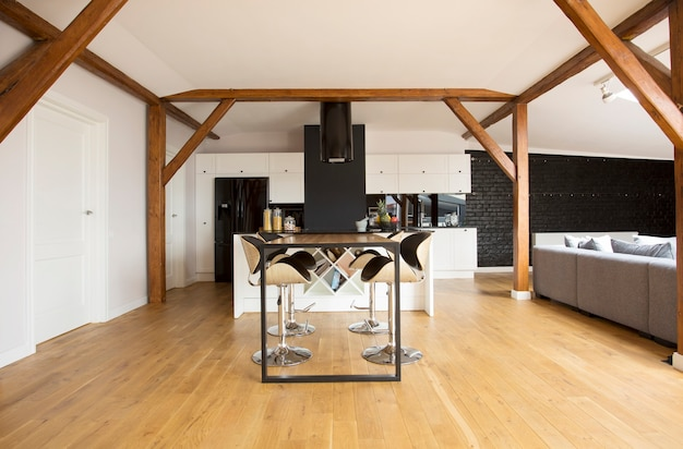 Tabourets de bar modernes et table noire à l'intérieur de l'appartement mansardé avec parquet, poutres et canapé gris