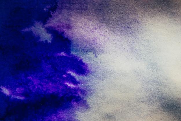 La tache d'encre s'étend sur la couleur bleue du papier