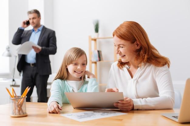 Tâche à enseigner. superbe femme énergique et travailleuse prenant sa fille au bureau