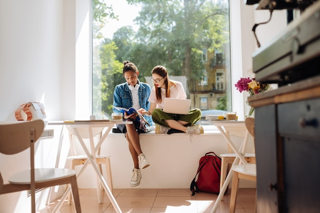 Tâche intéressante. joyeuse fille aux cheveux longs assise près de son amie et pointant vers le texte nécessaire