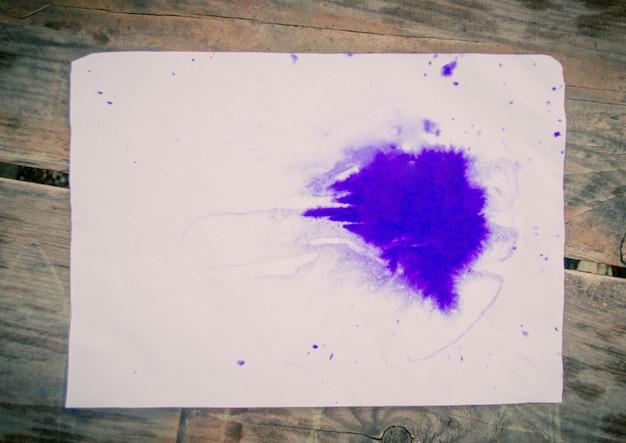 La tache pourpre de papier owhite de feuille vierge se trouve. tache bleue d'encre sur une feuille de papier blanc sur une surface en bois. toile de fond de base de base abstraite. espace pour le texte