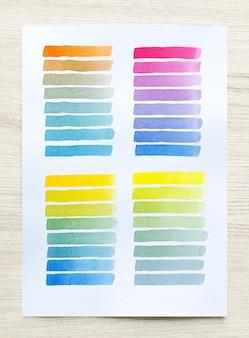 Taches d'aquarelle colorées sur papier blanc avec fond de bois. ensemble de rayures de pinceau aquarelle. coups d'encre. coup de pinceau plat. fermer.