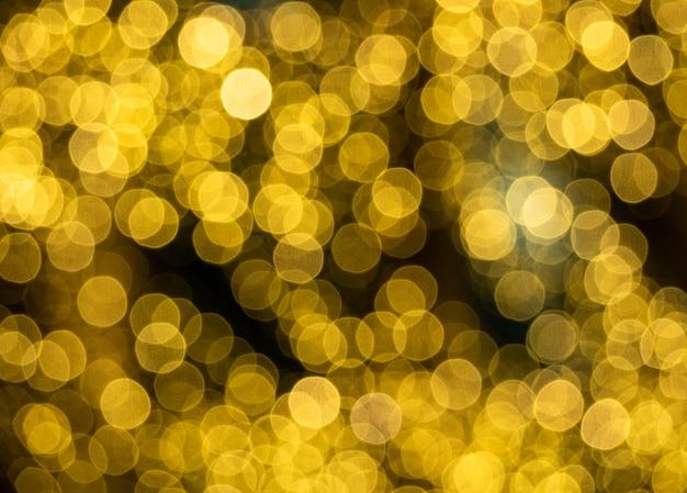 Taches de lumière dorées scintillantes sur fond noir. motif festif flou