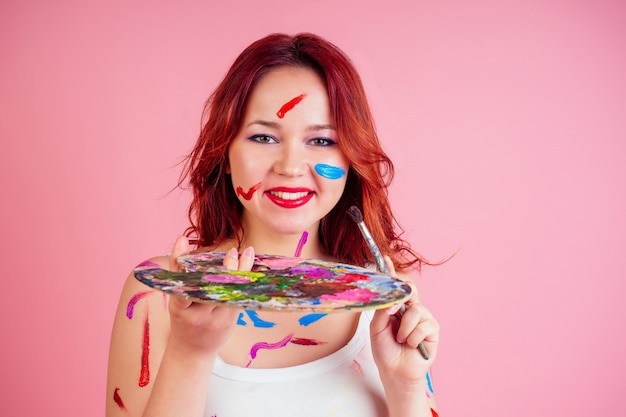 Taches de maquilleurs sales de peinture sur la palette du visage dans les mains sur fond rose en studio