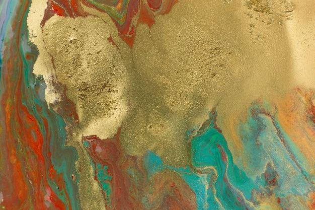 Taches d'or sur les taches rouges et bleues du motif abstrait de peinture